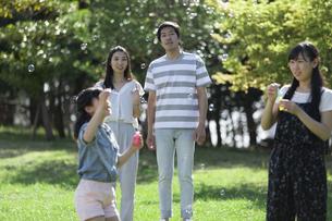 シャボン玉で遊ぶ家族の写真素材 [FYI04317287]