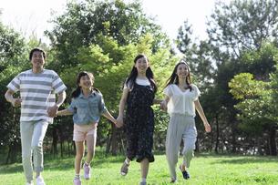 手を繋いで走る家族の写真素材 [FYI04317296]