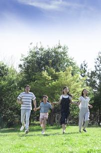 手を繋いで走る家族の写真素材 [FYI04317297]