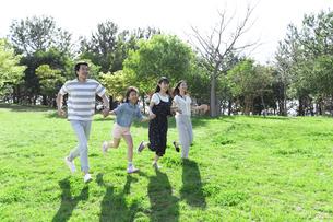 手を繋いで走る家族の写真素材 [FYI04317298]