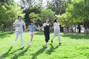 手を繋いで走る家族の写真素材 [FYI04317299]