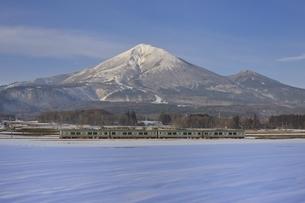 冬の磐梯山と電車の写真素材 [FYI04318388]