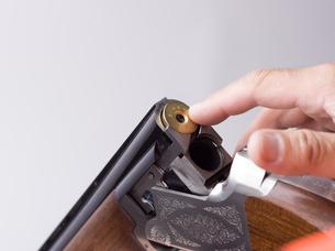 弾倉に弾をこめる手の写真素材 [FYI04318726]