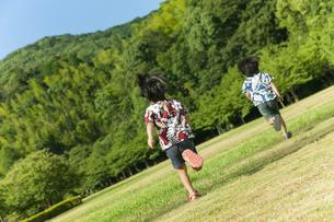 草原を走る双子の兄弟の写真素材 [FYI04318745]