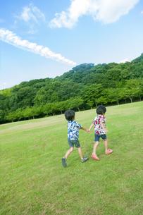 草原を走る双子の兄弟の写真素材 [FYI04318749]