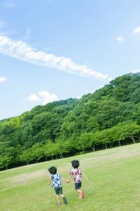 草原を走る双子の兄弟の写真素材 [FYI04318750]