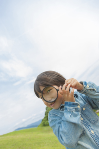 虫眼鏡を持って覗く日本人の男の子の写真素材 [FYI04318780]