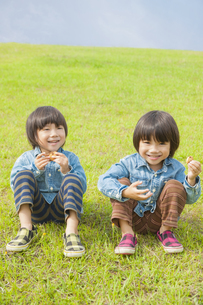 草原に座りお菓子を食べる双子の兄弟の写真素材 [FYI04318781]