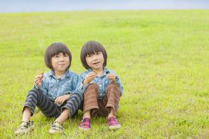 草原に座りお菓子を食べる双子の兄弟の写真素材 [FYI04318783]