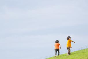 草原を走る双子の兄弟の写真素材 [FYI04318784]