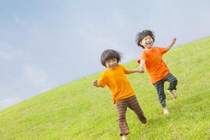 草原を走る双子の兄弟の写真素材 [FYI04318787]
