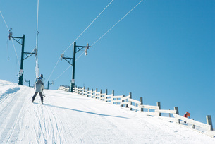 Young skier going up hill on ski liftの写真素材 [FYI04318815]