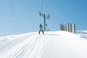 Young skiers going up hill on ski liftの写真素材 [FYI04318817]