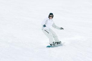 Teenage girl snowboarding on ski slopeの写真素材 [FYI04318840]