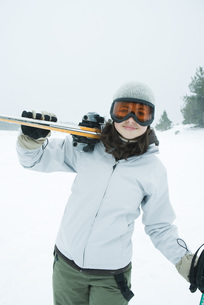 girl carrying skis on shoulder at cameraの写真素材 [FYI04318847]