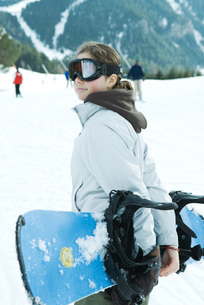 girl carrying snowboard behind backの写真素材 [FYI04318862]