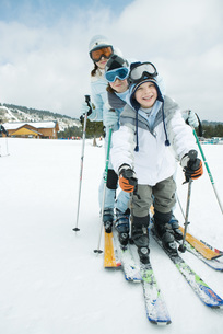 Three skiers standing together, lined upの写真素材 [FYI04318887]