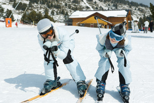 Two skiers crouching togetherの写真素材 [FYI04318889]