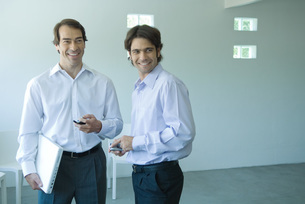 Two businessmen, each holding cell phoneの写真素材 [FYI04318925]