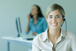 Woman wearing headset in officeの写真素材 [FYI04318954]