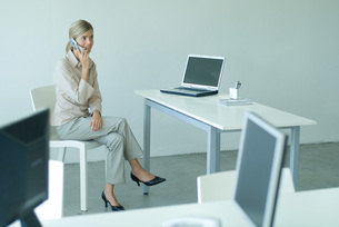 Woman seated at desk, using cell phoneの写真素材 [FYI04318961]