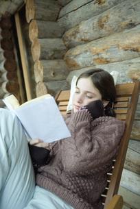 Teen girl in winter clothes reading bookの写真素材 [FYI04318977]