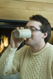 Man drinking hot beverage by fireplaceの写真素材 [FYI04318986]