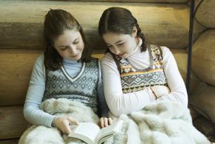 Two Girls sitting under warm blanketの写真素材 [FYI04318995]