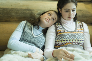 Two Girls sitting under warm blanketの写真素材 [FYI04318996]