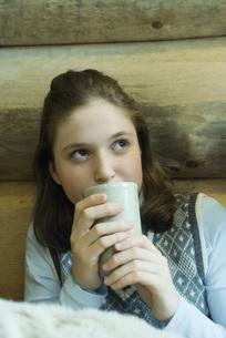 Teen girl drinking hot beverageの写真素材 [FYI04318997]