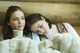 Two Girls sitting under warm blanketの写真素材 [FYI04318998]