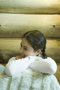 Girl sitting under warm blanket, smilingの写真素材 [FYI04318999]