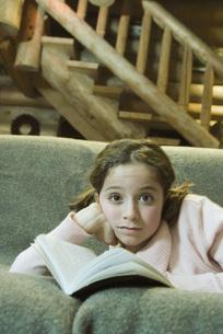 PreGirl lying on sofa with bookの写真素材 [FYI04319000]