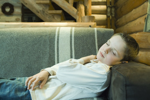 Preteen boy falling asleep on couchの写真素材 [FYI04319004]