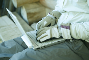 Man using laptop with gloves onの写真素材 [FYI04319007]