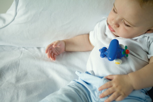 Sleeping baby with toy on stomachの写真素材 [FYI04319017]