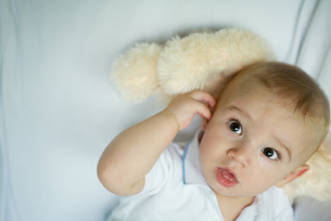 Baby lying with head on stuffed animalの写真素材 [FYI04319018]