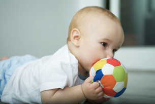 Baby on floor, holding ball up to mouthの写真素材 [FYI04319022]