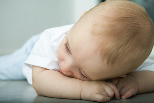 Baby lying on floor, resting head on armの写真素材 [FYI04319023]