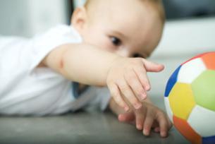 Baby on floor, reaching for ballの写真素材 [FYI04319024]