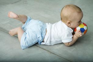 Baby lying on floor, biting on ballの写真素材 [FYI04319027]
