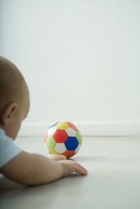 Baby lying on floor, looking at ballの写真素材 [FYI04319029]