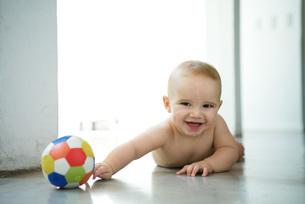 Baby lying on floor with ballの写真素材 [FYI04319043]