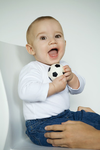 Baby sitting in chair holding ballの写真素材 [FYI04319076]