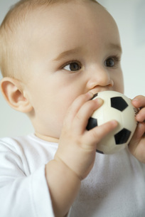 Baby putting toy soccer ball in mouthの写真素材 [FYI04319079]