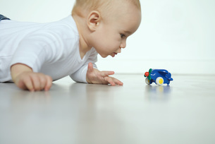 Baby lying and looking at toy airplaneの写真素材 [FYI04319088]
