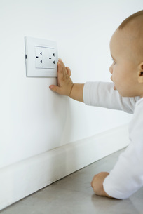 Baby reaching for electrical outletの写真素材 [FYI04319091]