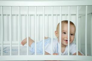 Baby looking through bars of cribの写真素材 [FYI04319106]