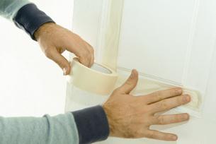 Man putting masking tape on doorの写真素材 [FYI04319107]