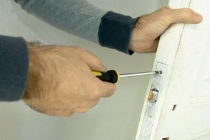 Man unscrewing look on door of handsの写真素材 [FYI04319108]